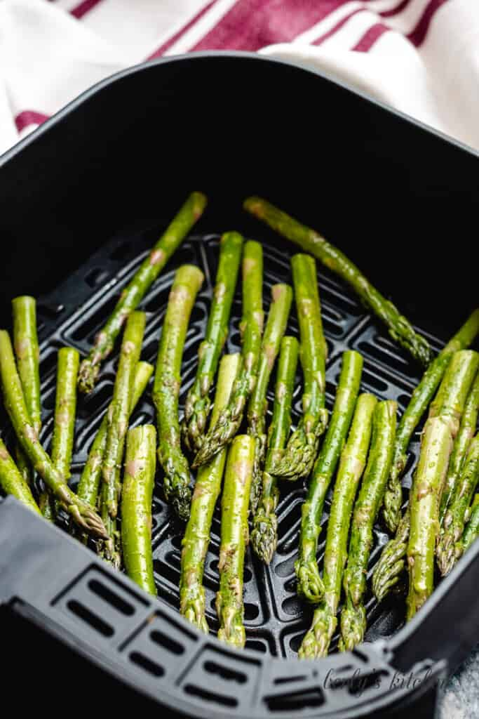 The raw asparagus placed in the basket to cook.