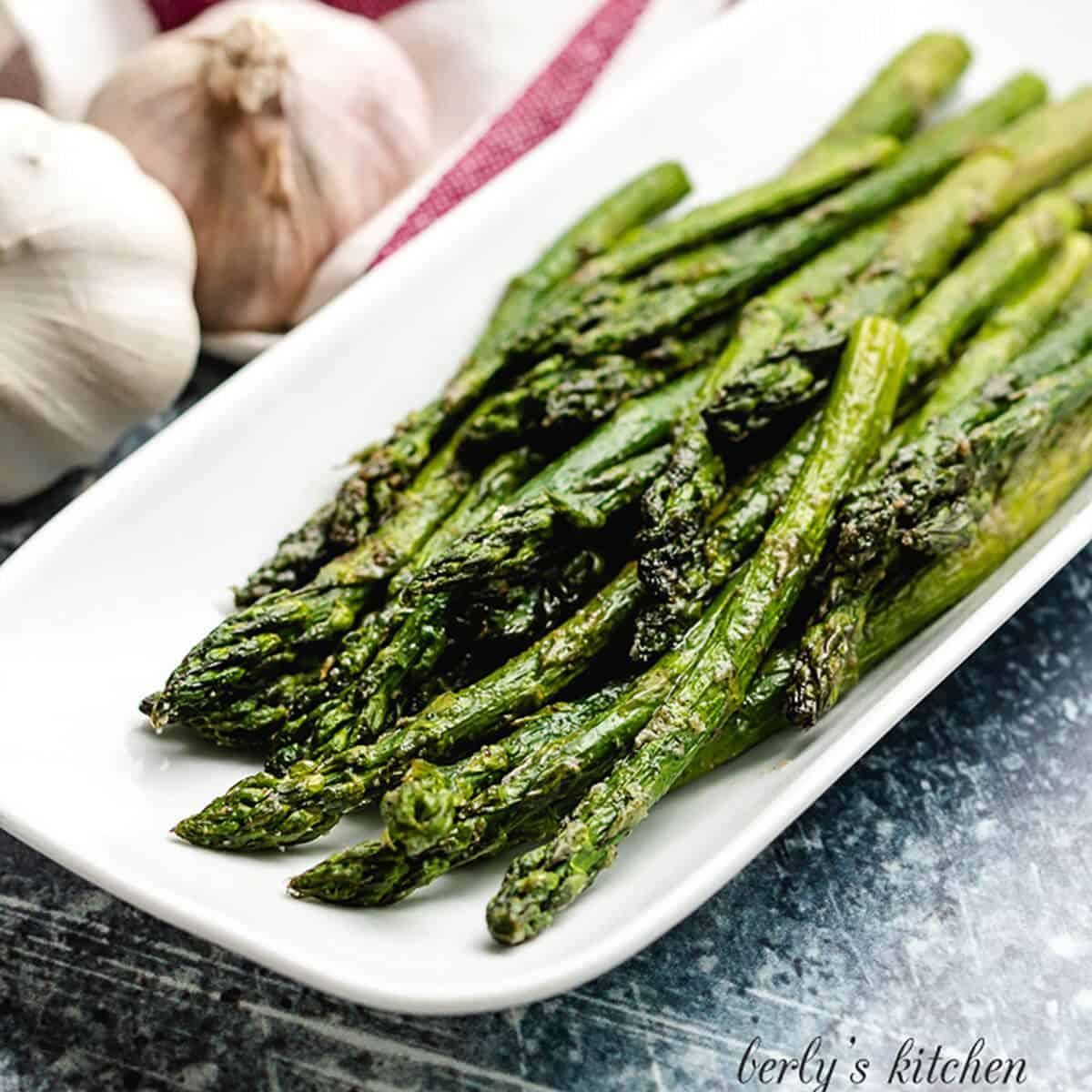 Seasoned air fryer asparagus served on a platter.