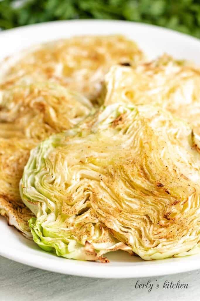 Four pieces of cooked cabbage on a white plate.