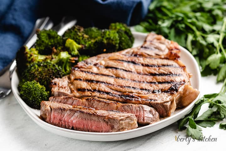 A sliced steak served on a plate with broccoli.