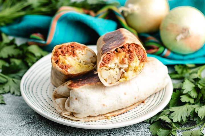 A sliced chorizo breakfast burrito stack atop a whole one.