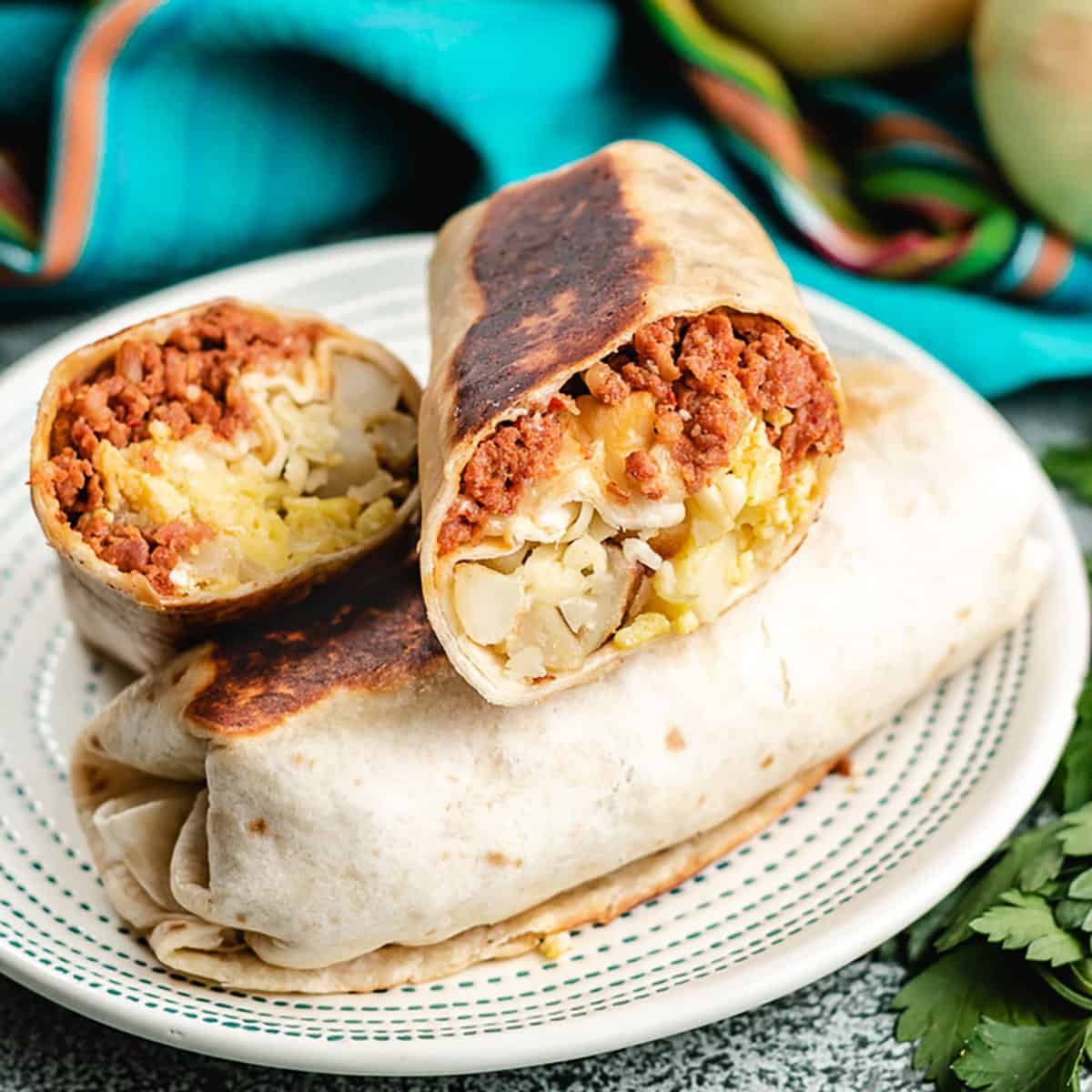 Two chorizo breakfast burritos on a plate.