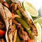 Up-close view of a fajita served with a halved lime.