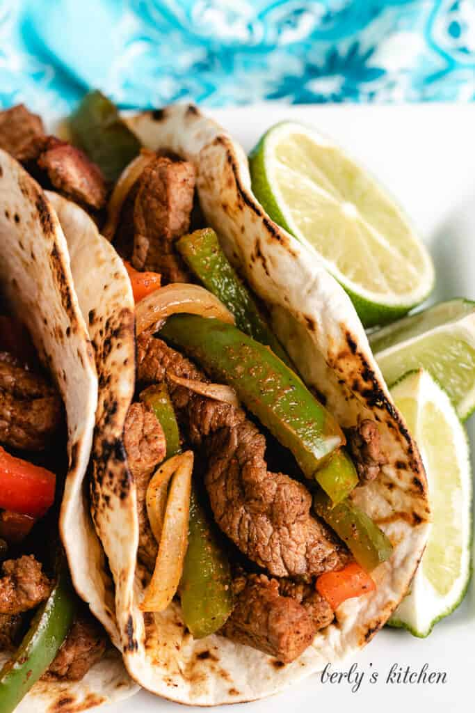 Up-close view of a fajita served with a lime wedge.