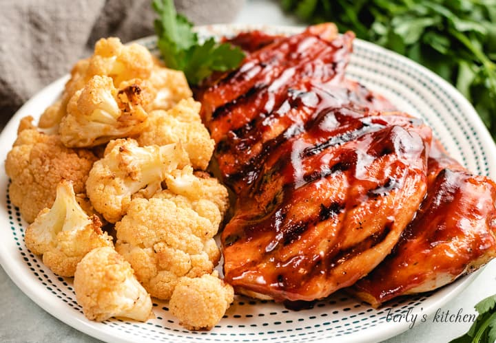 Two grilled BBQ chicken breasts with air fryer cauliflower.