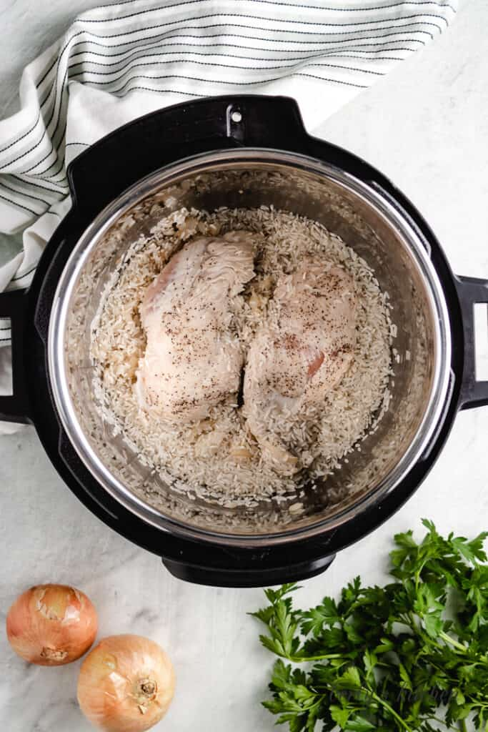 Chicken, onions, rice, and broth in the instant pot.