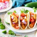 Three Instant Pot street tacos with chicken filling and diced onions.
