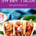 Three street tacos with chicken topped with onions and tomatoes.