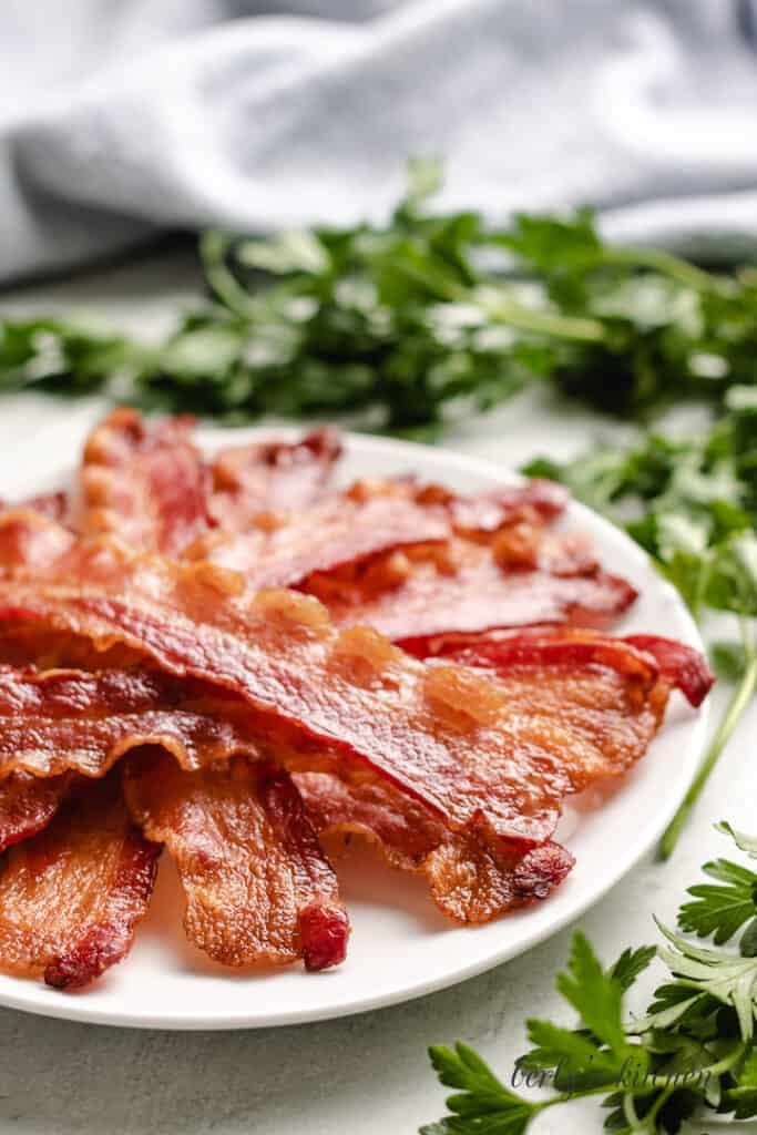 Strips of cooked bacon on a plate.