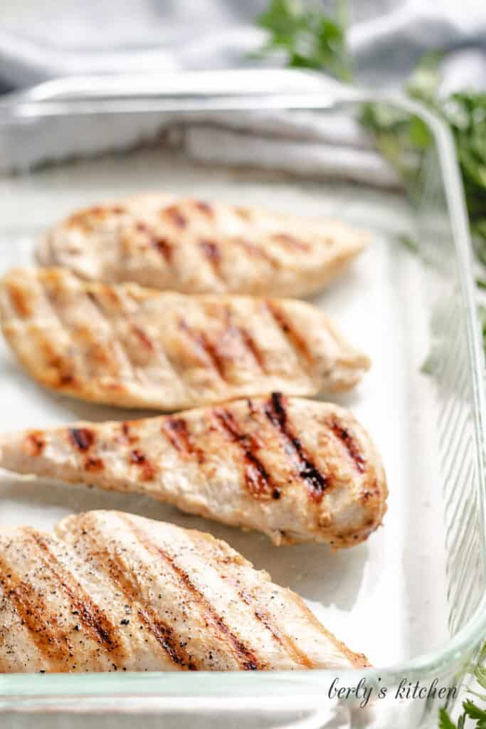 Four chicken breast cutlets in a large baking dish.