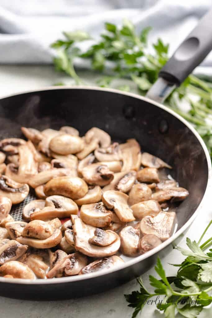 Mushrooms being sauteed in a pan with butter.