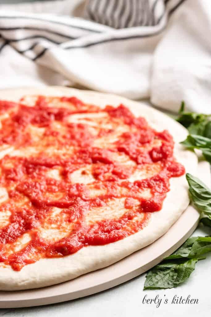 Marinara sauce has been spread over the dough.