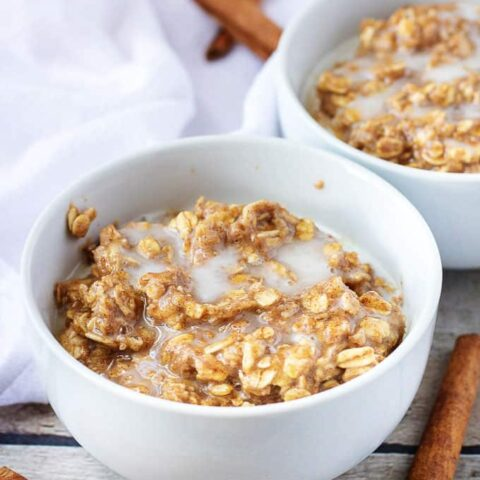 Two white bowls with cinnamon oatmeal.