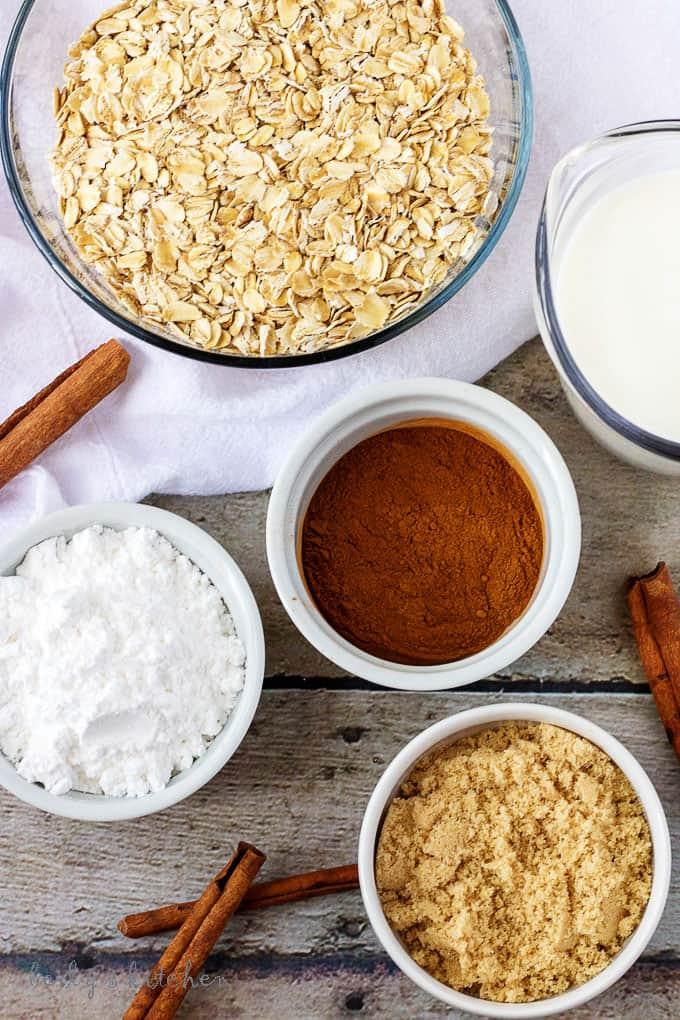 Top down view of ingredients for oatmeal (cinnamon, oats, milk, and brown sugar).