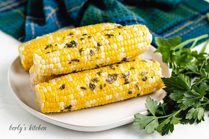 Four pieces of grilled corn on the cob on a plate.