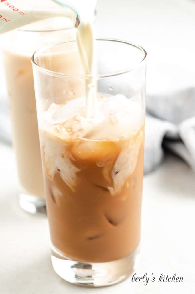 Milk being poured into the iced coffee.