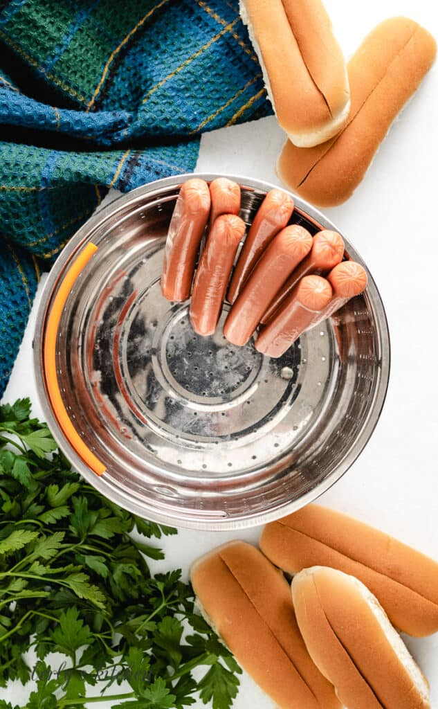 Uncooked hot dogs in a steamer basket.