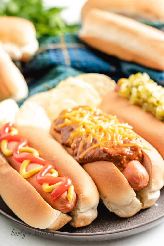 Three cooked sausages in buns with toppings.