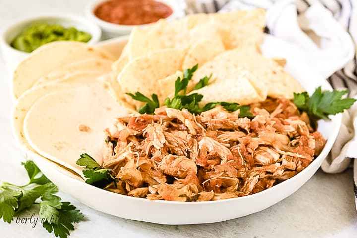 Salsa chicken in a bowl with tortillas.