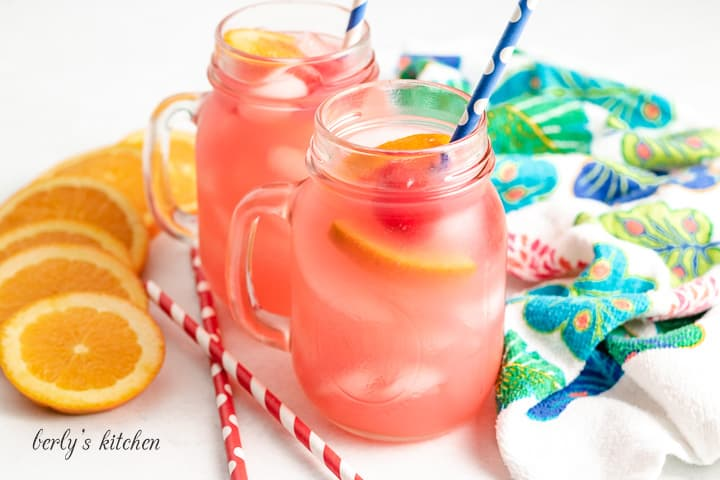 Tropical vodka punch served in mugs with fresh fruit.