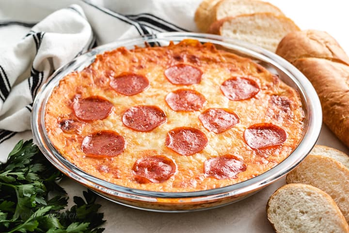 The baked pepperoni pizza dip in a pie pan.