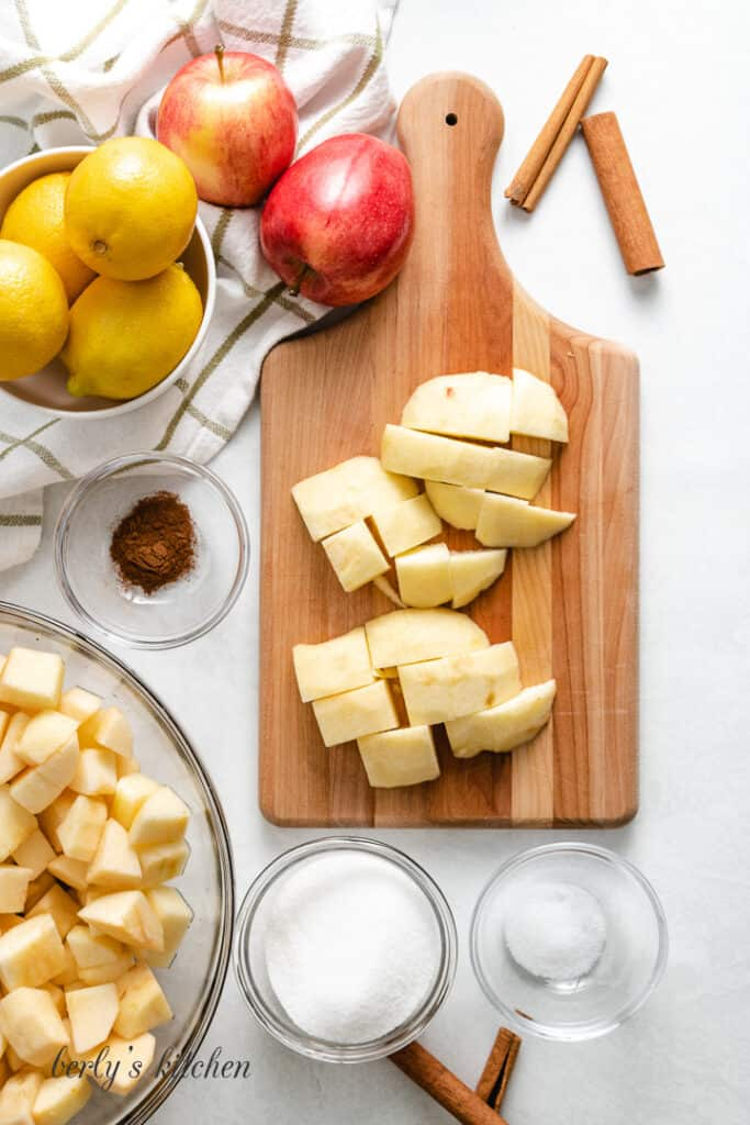 Diced apples on a cutting board surrounded by ingredients.