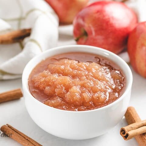 The applesauce surrounded by fresh cinnamon sticks and apples.