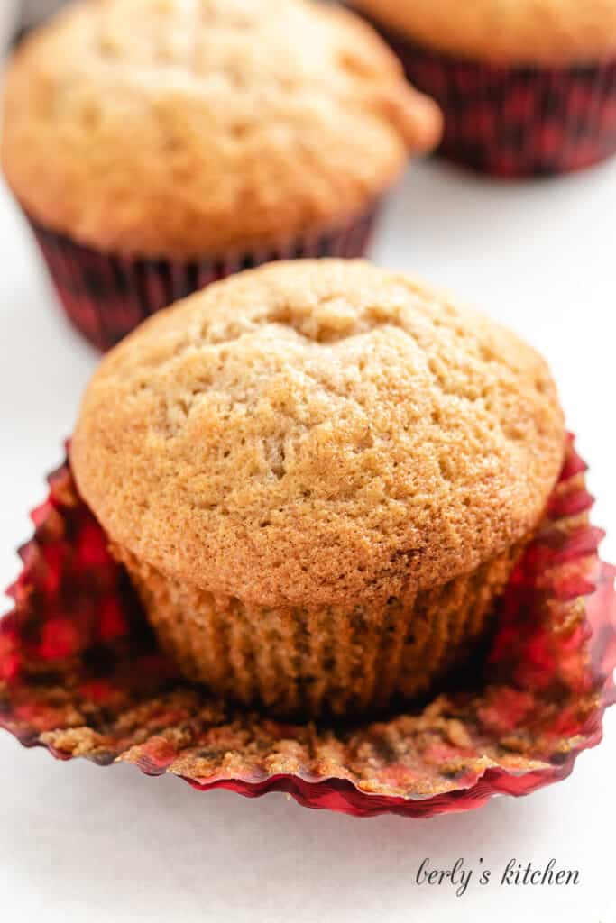 A muffin with it's liner pulled away.