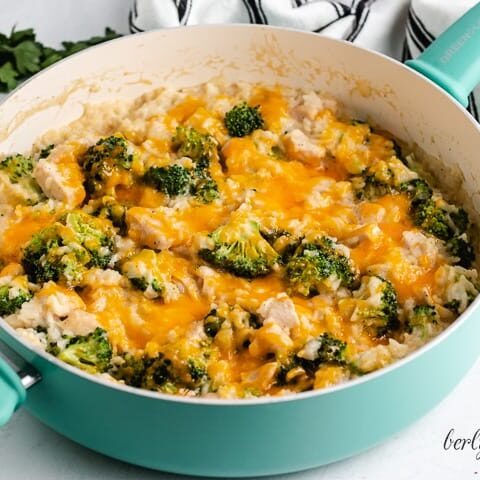 A blue skillet filled with cheesy chicken rice and broccoli.