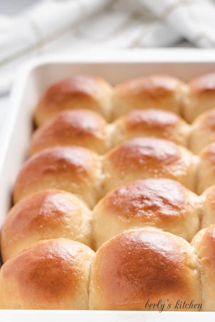 Baked Hawaiian rolls sitting in a baking dish.