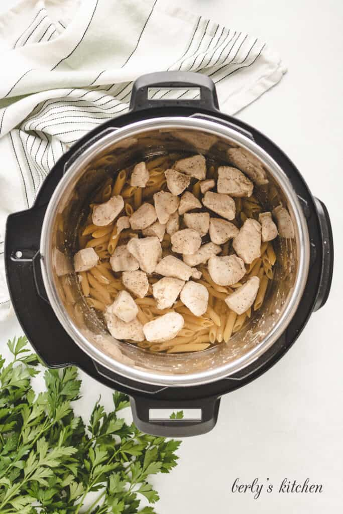Chicken on top of noodles in a pressure cooker.