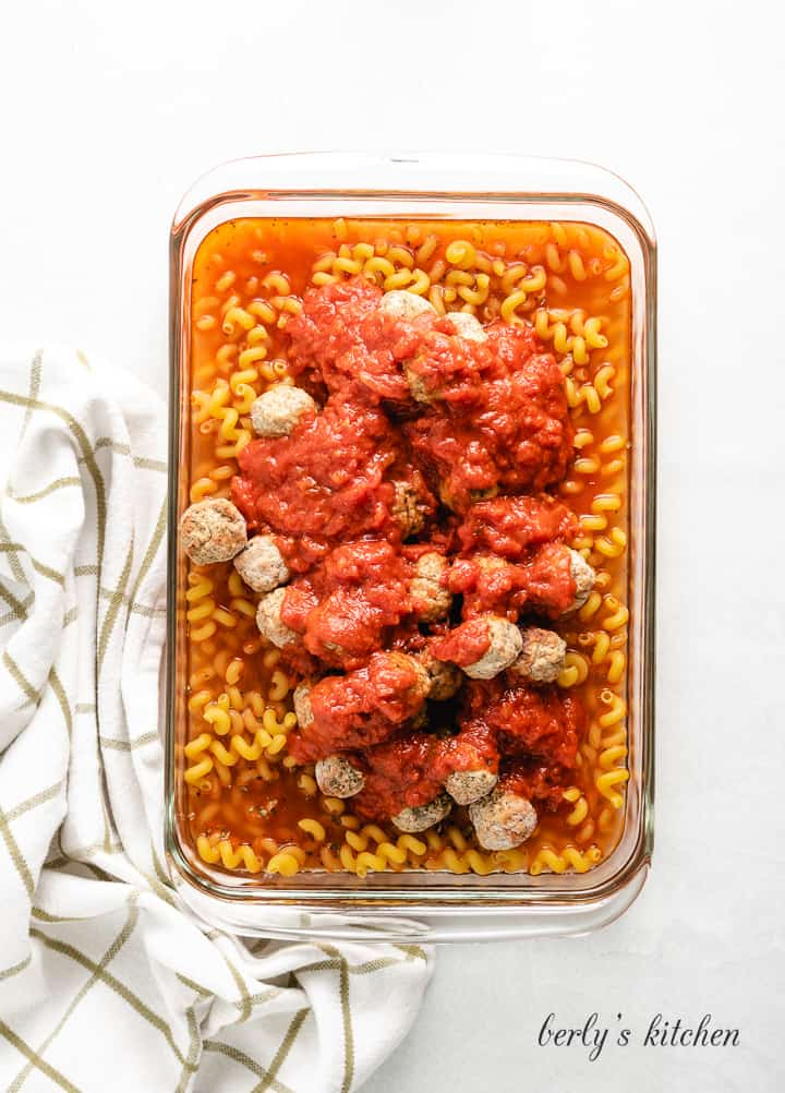 Marinara, meatballs, and other ingredients in a casserole dish.