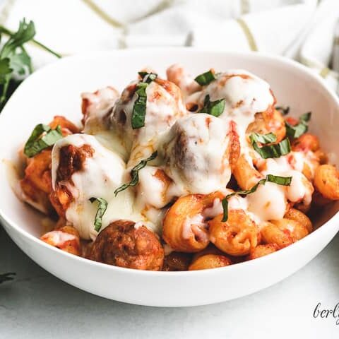 Meatball casserole in a bowl topped with cheese.