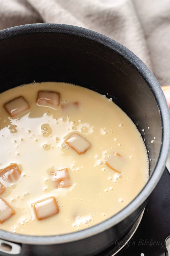 Caramel squares and sweetened condensed milk in a pan.