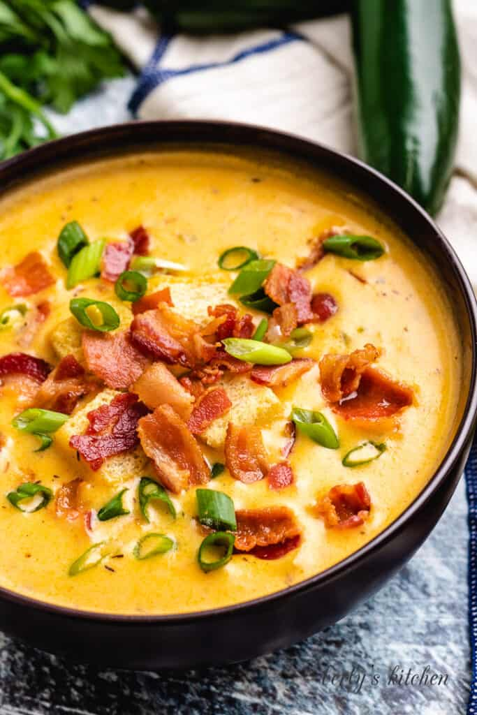 Cheesy beer soup topped with onions and bacon.
