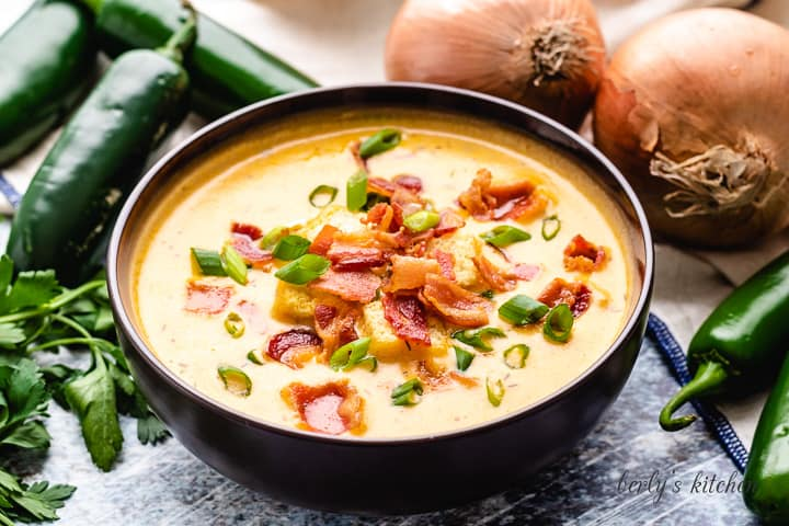 Beer cheese soup garnished with bacon and green onions.