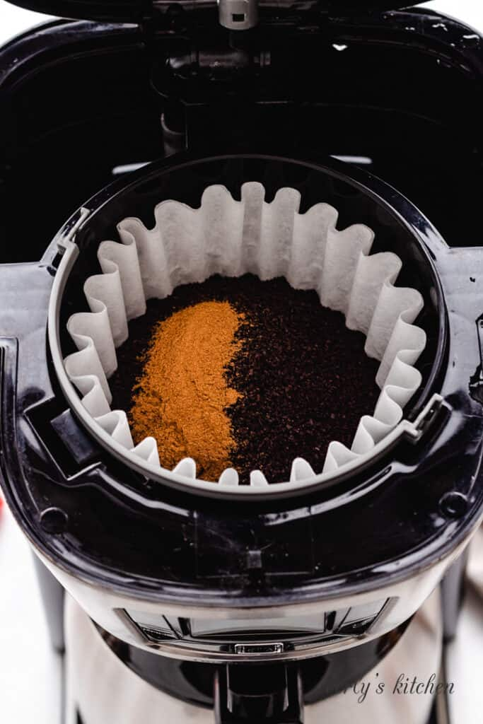 Ground coffee and cinnamon in a coffee maker.
