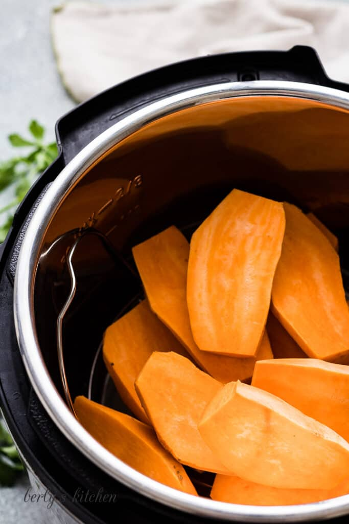 Slices, raw sweet potatoes in a pressure cooker.