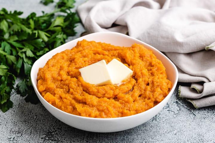 A white bowl loaded with Instant Pot mashed sweet potatoes.