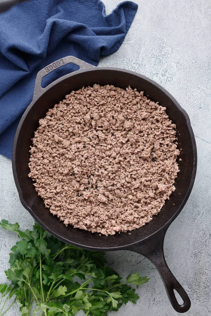 Ground beef cooking in a cast iron skillet.