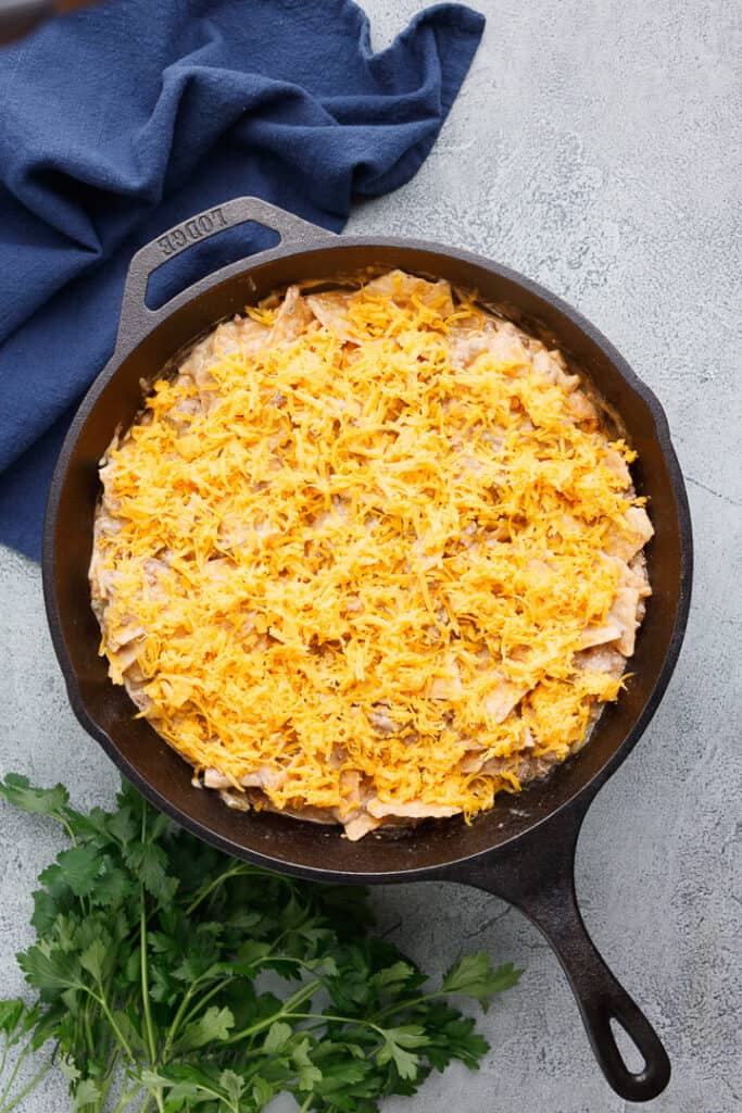 Shredded cheese added to the skillet.
