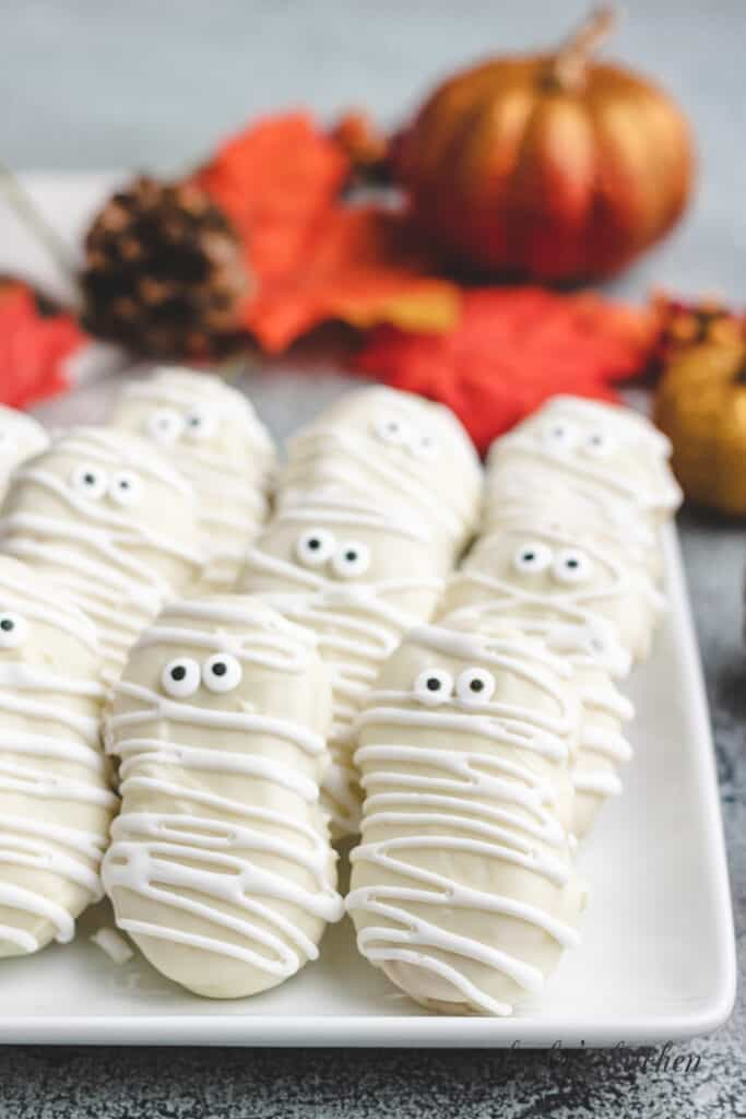 Nine mummy cookies on a plate.