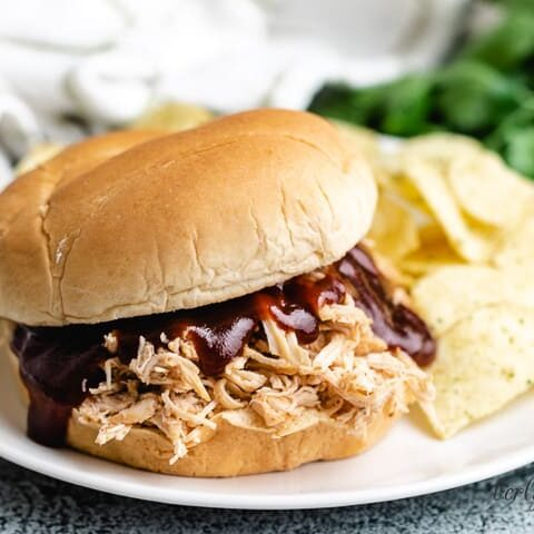A slow cooker BBQ chicken sandwich on a plate.