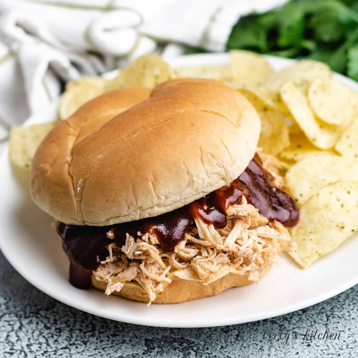 Slow cooker BBQ chicken on a bun with chips.