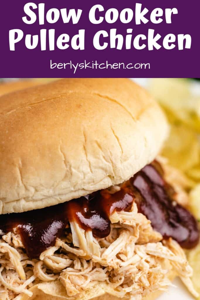 Slow cooker BBQ chicken breast on a bun with BBQ sauce.