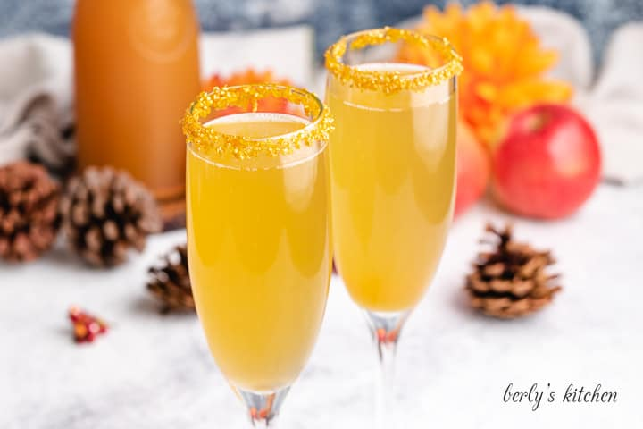 Apple cider mimosas in champagne glasses rimmed with golden sugar.