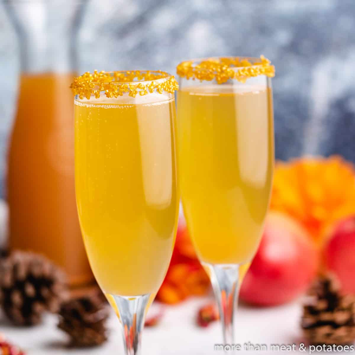 Two apple cider mimosas in champagne glasses.