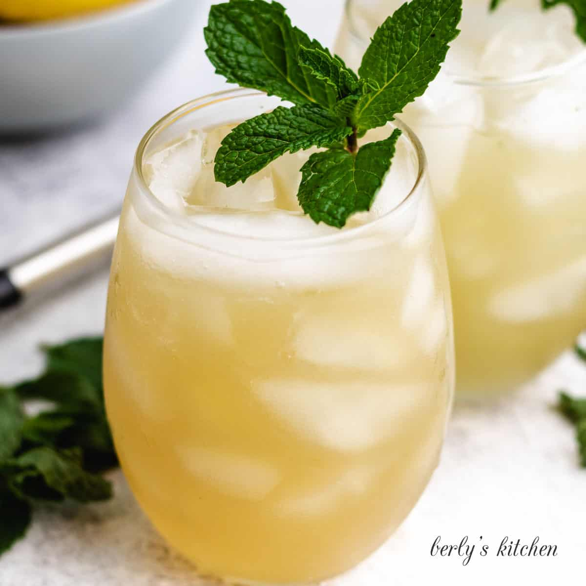 Two bourbon smash cocktails garnished with mint.