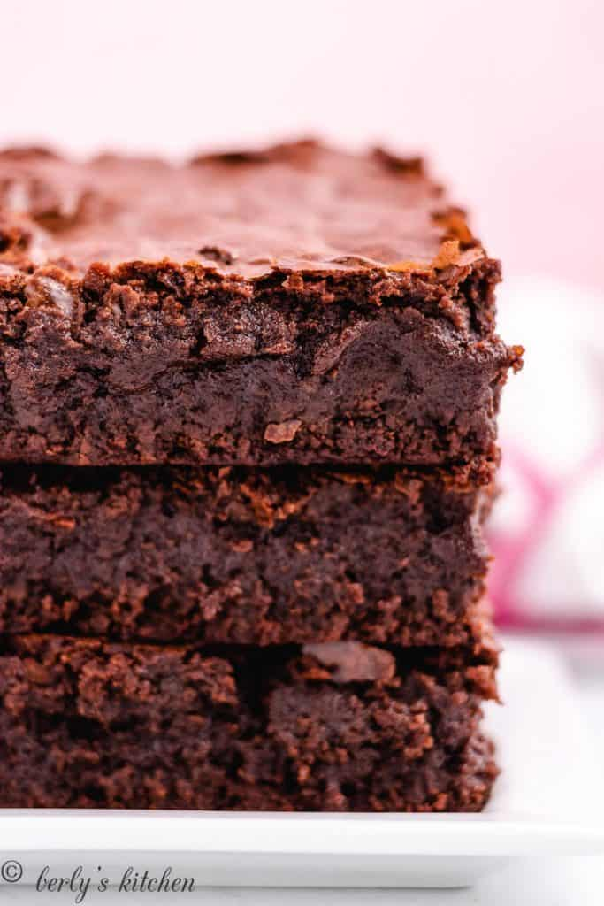 Three fudgy brownies stacked on a plate.