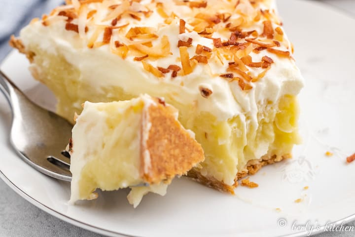 A piece of the coconut cream pie cut with a fork.